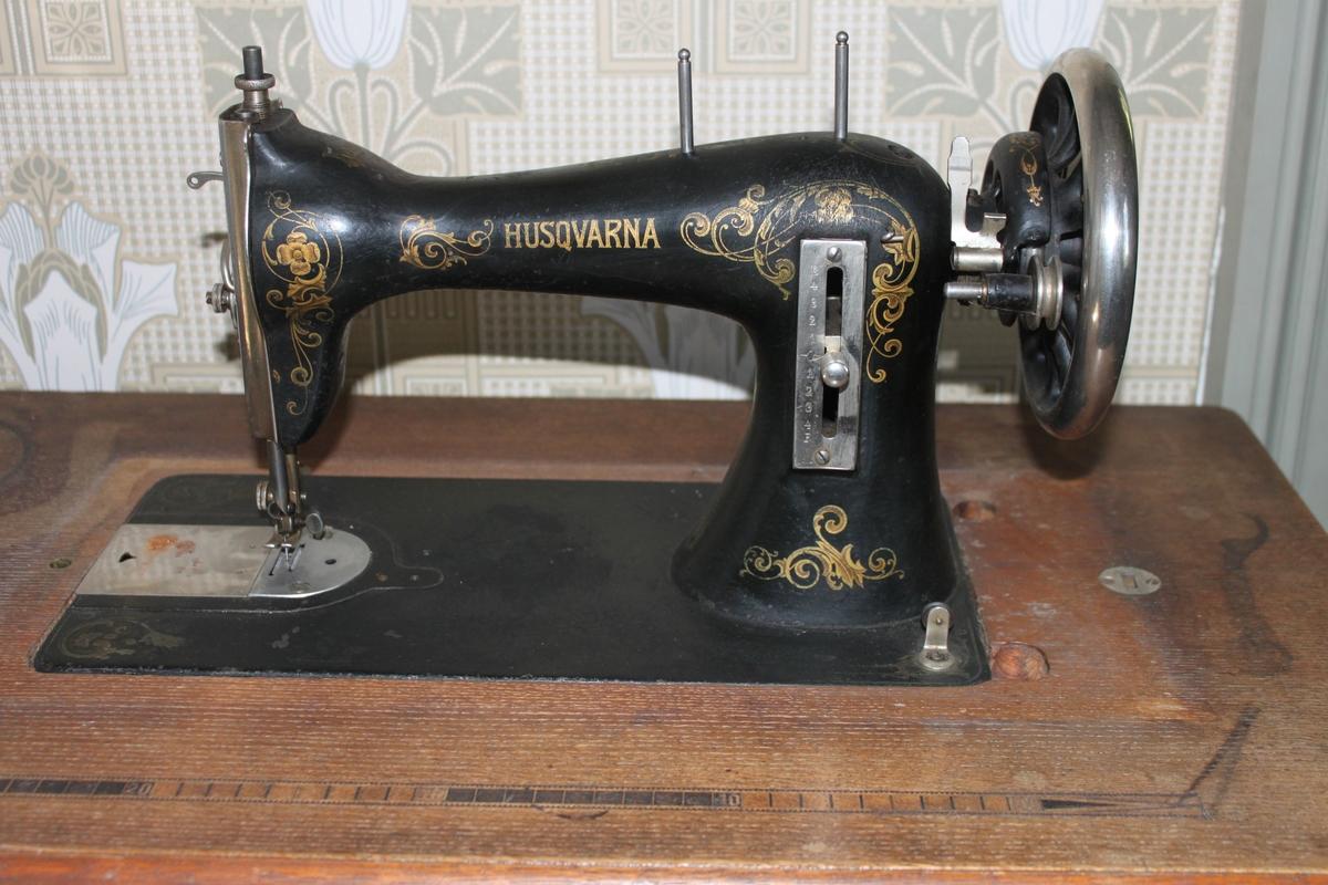 Symaskin, trampmodell av märket Husqvarna. Maskinen har  en gjuten benställning med tramp och drivhjul. Bord av trä med smal draglåda under skivan, innehållande sybehör. I bordsskivans yta är ett måttband i intarsia infällt. På maskinens front mönster i guld med blomslingor och firmanamn. Maskinen har huv av formpressat trä med handtag av metall.