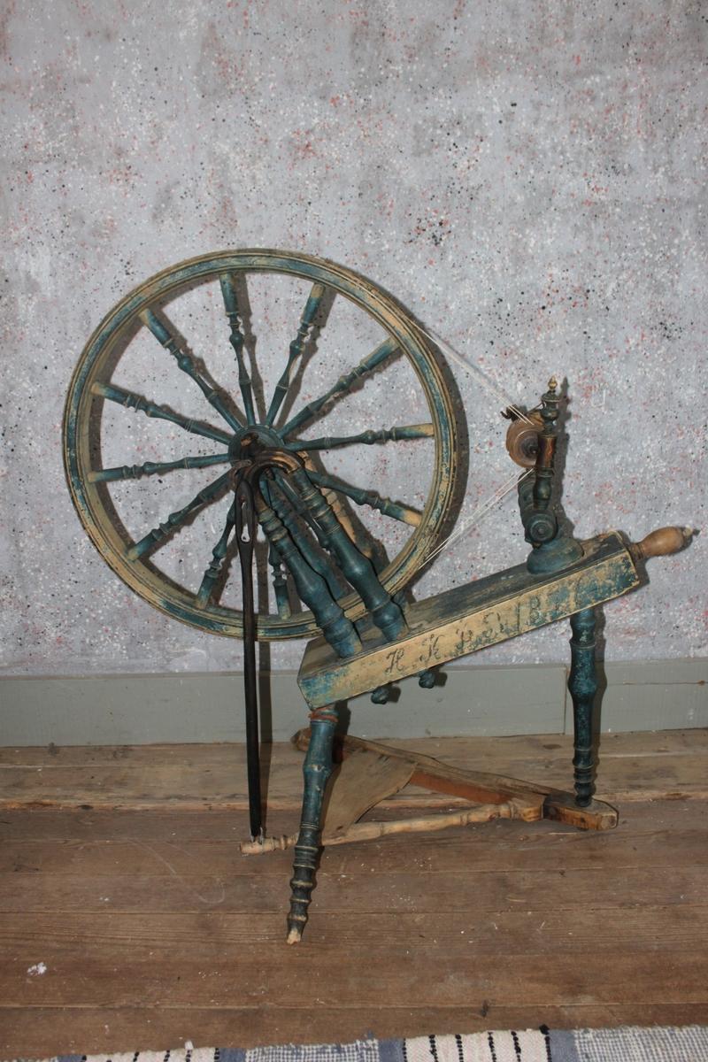 Blå spinnrock med kraftigt svarvade detaljer. Drivhjulet monterat på två upprättstående, svarvade, u-formade ståndare. Tolv svarvade ekrar. Hjulet drivs av en trekantig trampa, förbunden med vevaxeln via en vevstake. Nav och vevaxel av järn. Liggande vingdon. Rockarm med tillhörande delar saknas.