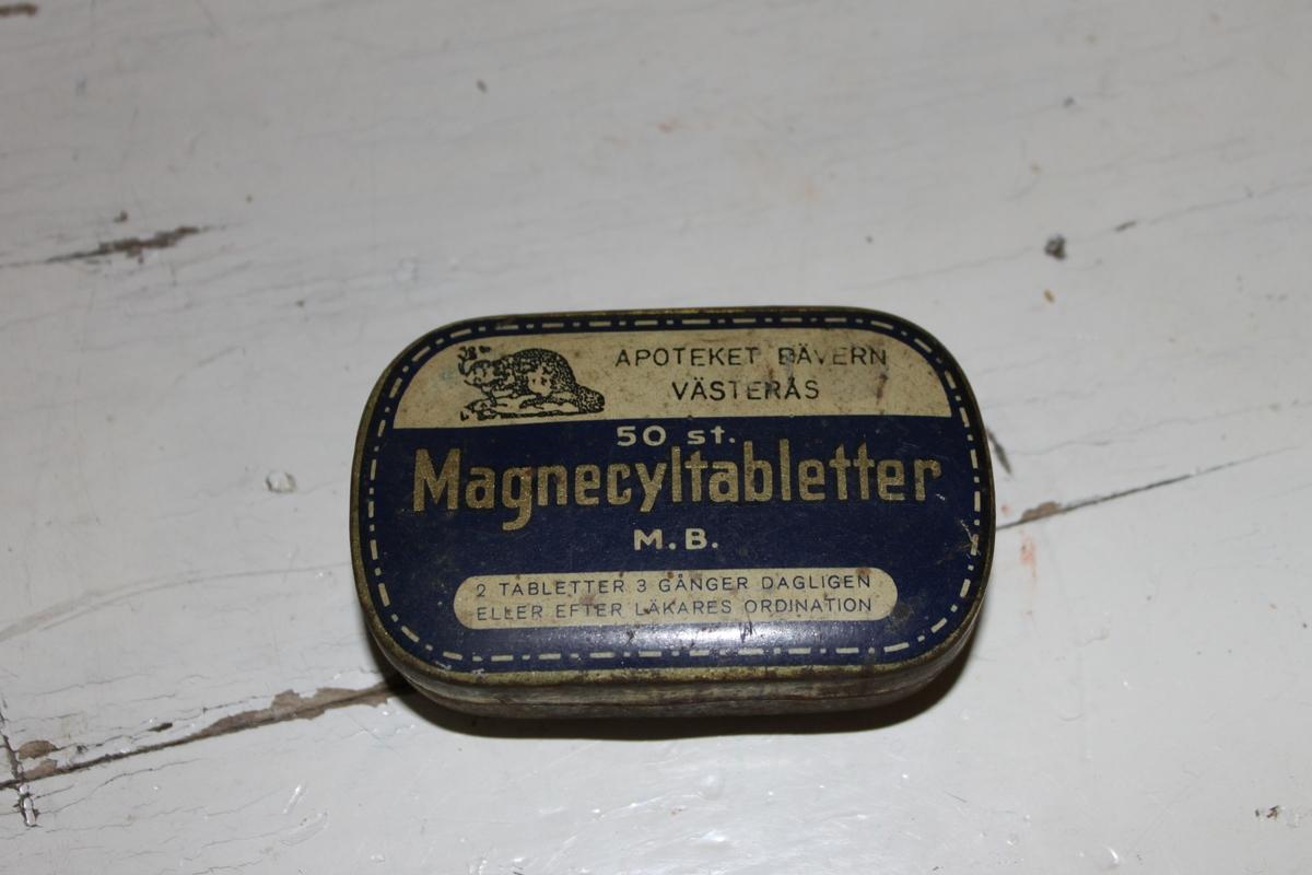 Plåtask till Magnecyltabletter. Fyrkantig ask med rundade hörn. Guldfärgad med blått lock.