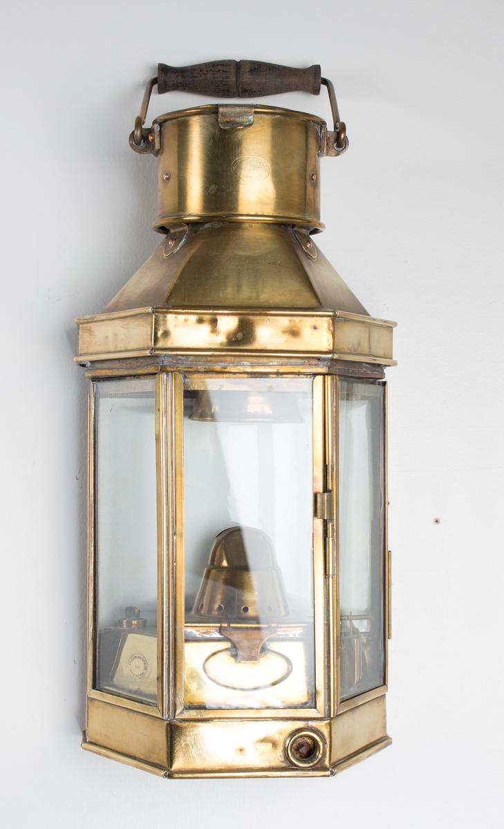 Parafinlykt med sekskantet lampehus med glass, håndtak og veggfeste.