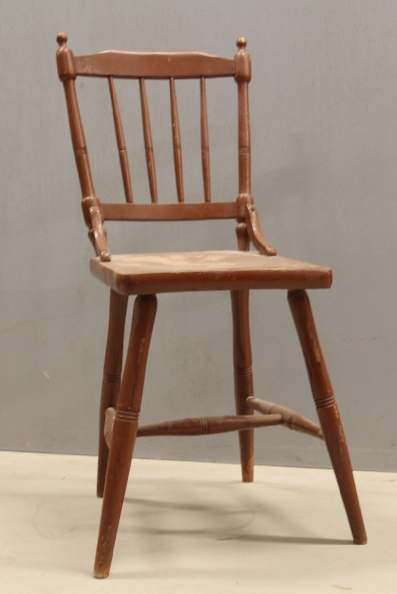 Pinnestol av tre. Høye ben og lav rygg. Hformet sarge mellom fire rette ben. Dreiet spiler og noe på bena. Malt brun.