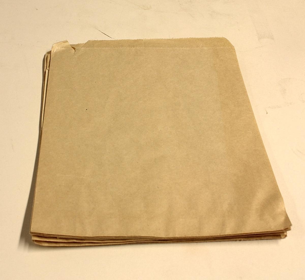 7 stykk rektangulære poser i glatt, brunt papir. Gjerne brukt i forbindelse med salg av søtsaker ol.