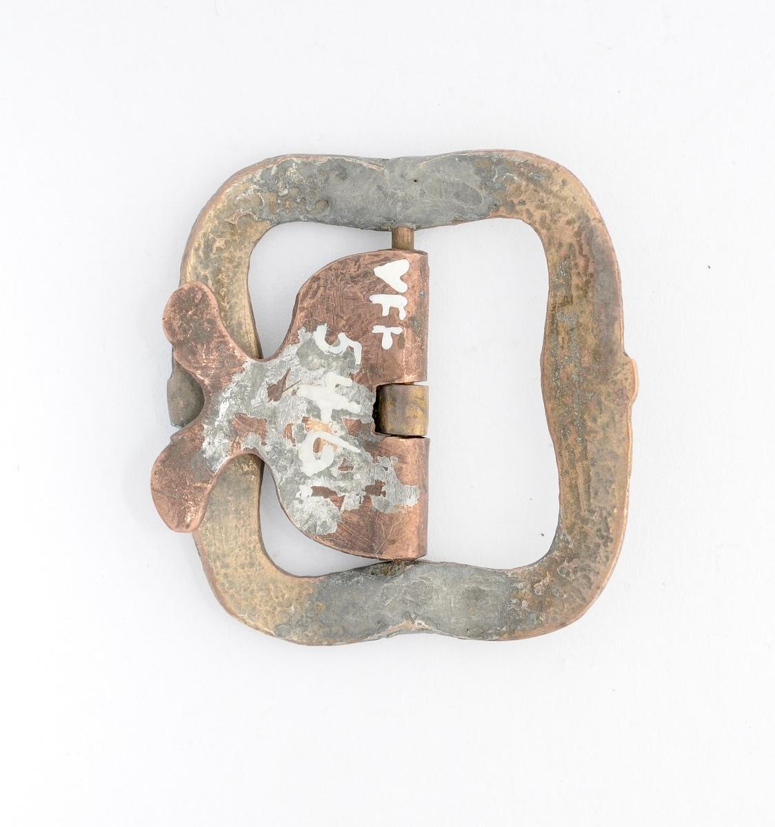 Knebandspenne støypt i messing. Rektangulær form. Lite bøygd. Stolpe, kalv og tann smidd i kobber. Reparert ved stolpefeste.