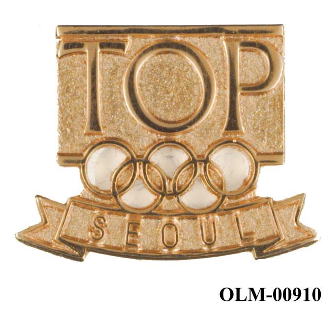 Merke i gull fra Seoul'88, teksten TOP øverst, de olympiske ringer i midten, og et banner med teksten SEOUL nederst.