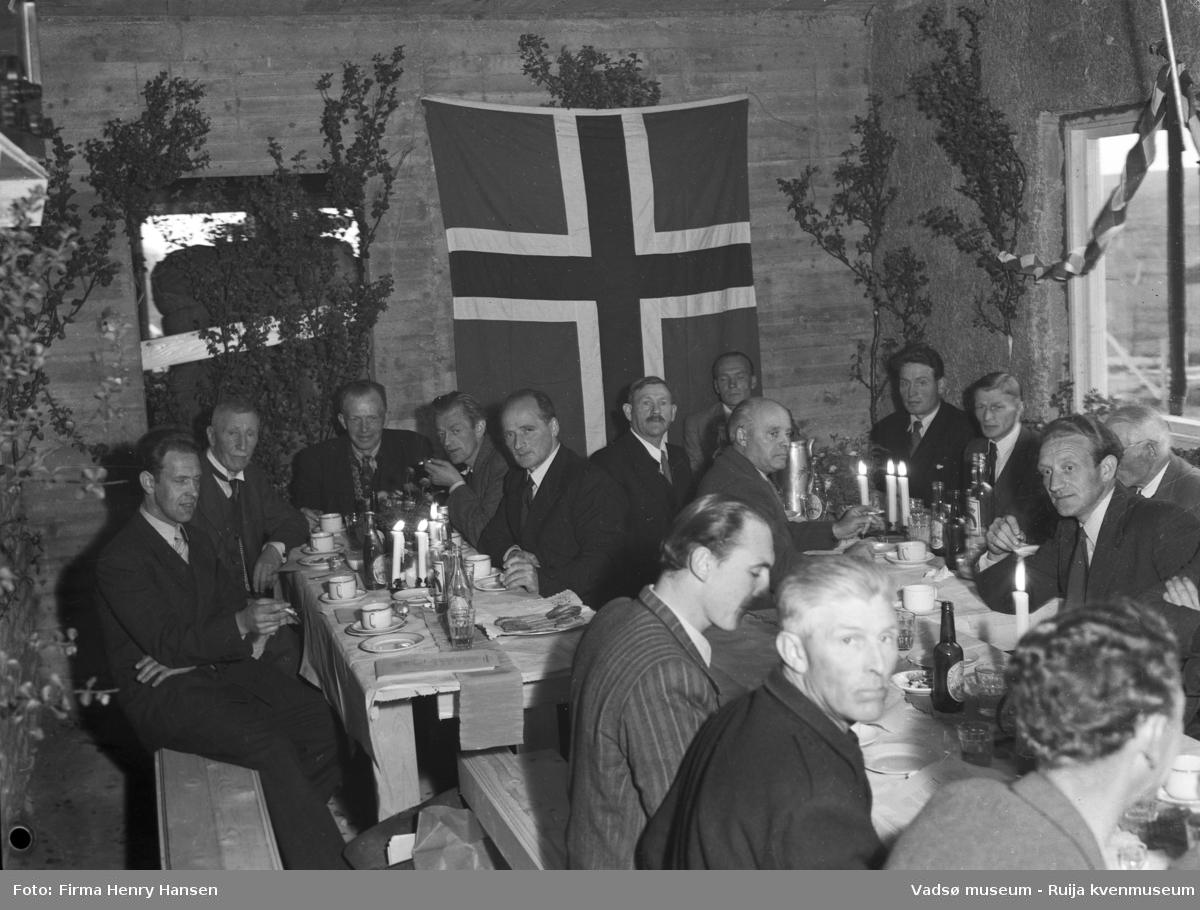 Bildet viser kranselaget på Finnmark Kringkaster i august 1948. Vi ser et langbord dekket med flasker og glass. Rommet er pyntet med løv og norske flagg.