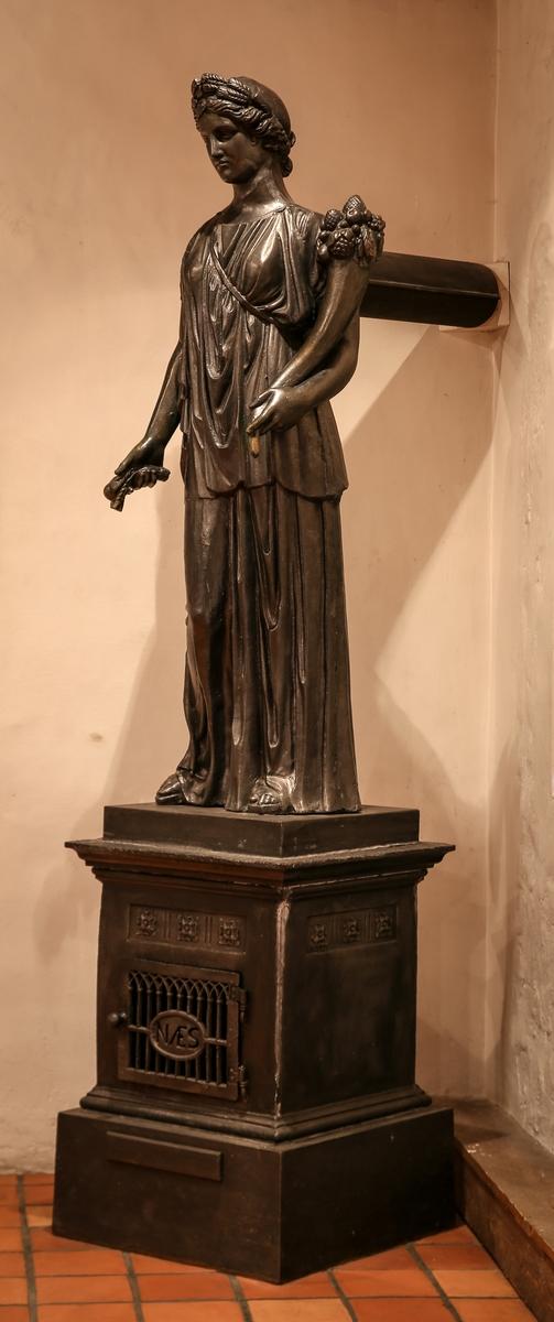 Statuen står på en firkantet sokkel, fyrkammeret, med firkantet gitterdør merket med NÆS. Statuen er en kopi av drapert antikk kvinnefigur, kronet med hvetekrans og overflødighetshorn i sin venstre og kornaks i sin høyre hånd. Avtrekk gjennom ryggen.