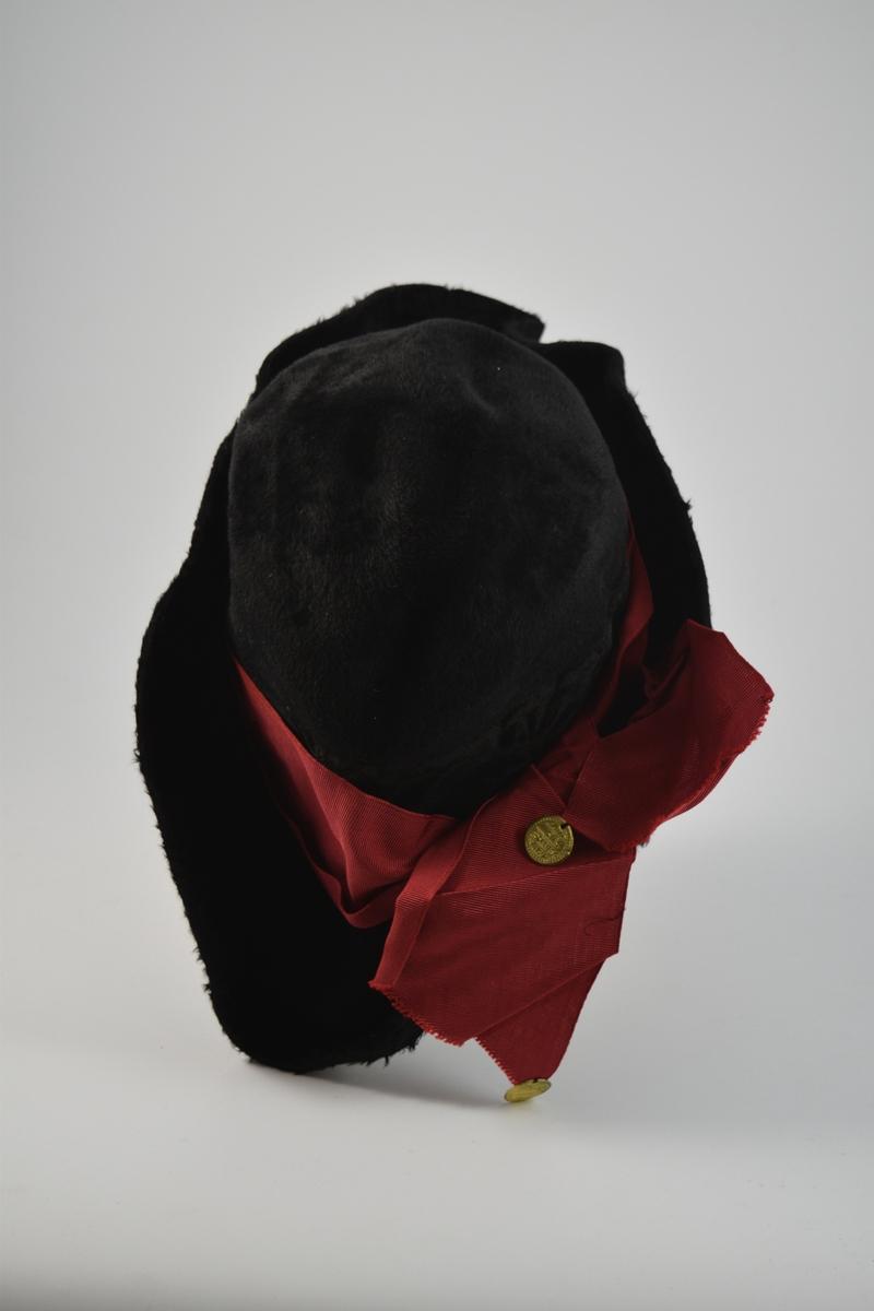 Form: sirkulær/ oval, båtform. Pullen oval, nesten spiss i endene. Grop i hetten topp. Oppad liggende brem. Rødt bredt hatteband, ripsbånd, rundt hele pullen, knyttet sammen på den ene siden. To plast paljetter dekket av gullfarge ligner mynter og er festet i endene av båndet.  En spenne med diamantlignende pryd er festet til den andre siden av hatten. Renessansestil (?)
