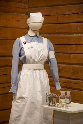 Sykepleieruniform på en dukke, med utstyr på et bord ved siden av.