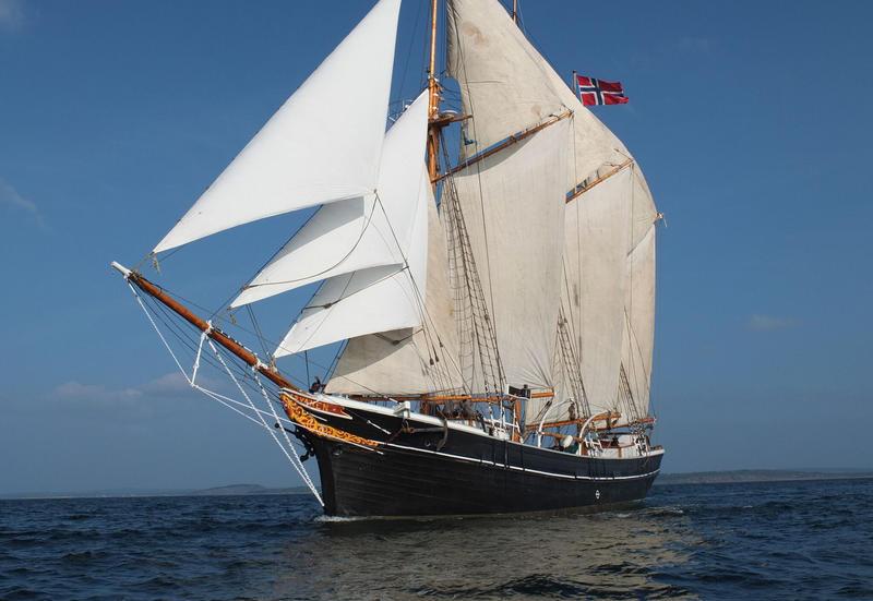 """Skonnerten """"Svanen"""" med tre master og for fulle seil ute på vannet, med norsk flagg, sett fra babord. (Foto/Photo)"""