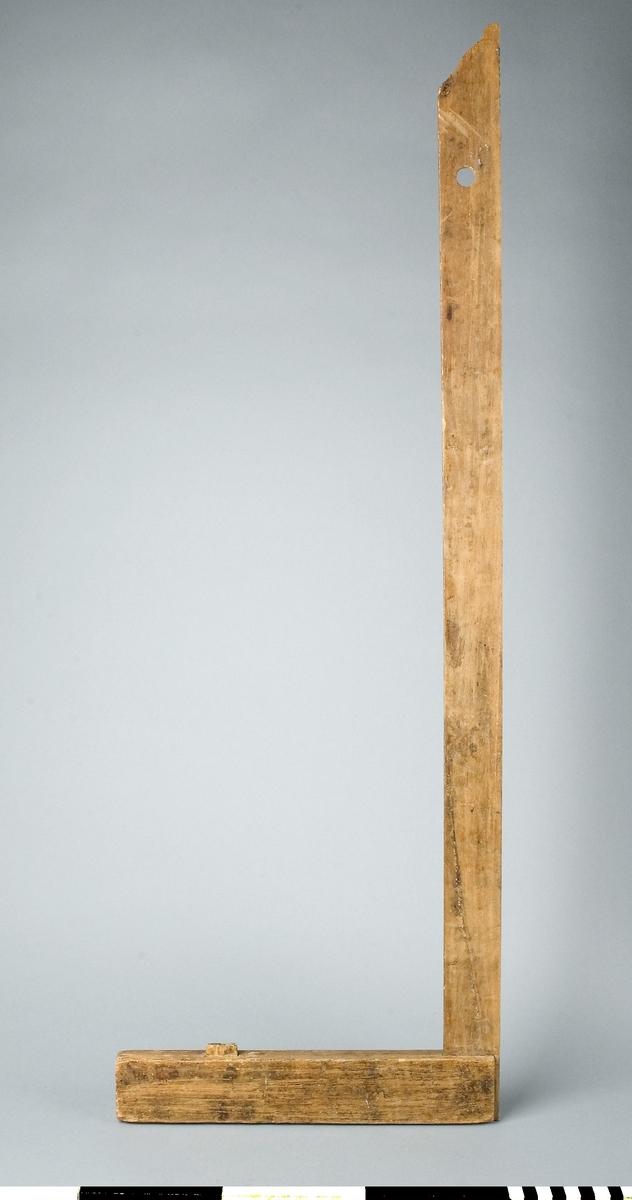 Vinkelhake av trä. Anslag av ek och linjal av bok. Vinkelmått för mätning av vinkel 90 grader. Anslaget har en tapp på mätsidan för stöd vid mätning. Den yttre änden av linjalen är profilsågad i dekorativt syfte. Nött. Färg- och limfläckar. I linjalens övre del finns ett hål för upphängning.  Kommer troligen från Dahlgrens snickeri i Nacka.  Funktion: Markering av 90° vinkel på arbetsstycke