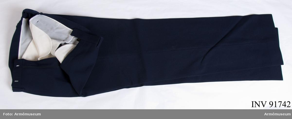 """Långbyxor sydd i blått kläde. Syntetfoder. Etikett på insidan: """"Hjelm exclusive, made in Sweden, kunglig hovleverantör, svenskt! det lönar sig"""". Storlek C 48."""