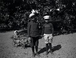 Tre barn som leker med en liten vagn på Tuna gård.