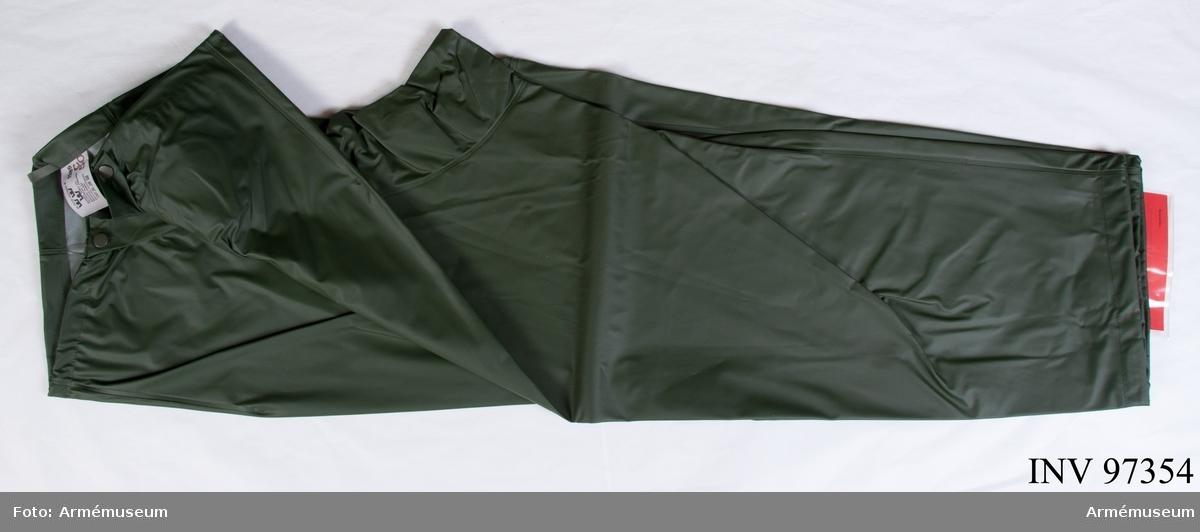 """Byxor av grön PVC-belagd polyamid, med tryckknappar. Vdihängande etikett: """"Försvarets materielverk, Originalmodell, M 7379-127000-5, Regnställ byxor, 1985-11-06, Elisabeth Rönnberg, Int T, Göran Olmarker Q Int T"""". Etikett på insidan: """"M 7379-127000-5, 1985, Rukka Turo Oy, tillverkad i Finland, 80 % PVC plast 20 % plyamid, skötselanvisning, C 50""""."""