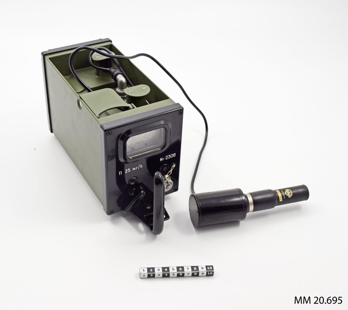 """Intensimeter i hölje av lättmetall, grönmålad. Ovansidan försedd med bärhandtag samt fönster för visarinstrument och manöverorgan, samt huvudomkopplare för olika mätområden. I sidan finns uttag med GM-rör (Geiger-Muller). I lådan finns batteribox med förlängningskabel och kopplingsdon, bärsele, plastpåsar med klämmor, skruvmejsel samt bärsele. Transportlåda av ek, fernissad, bärhandtag av läder. Lock överst med märkning: materielnummer och benämning samt: """"modifierad"""". Individnummer: 2306."""