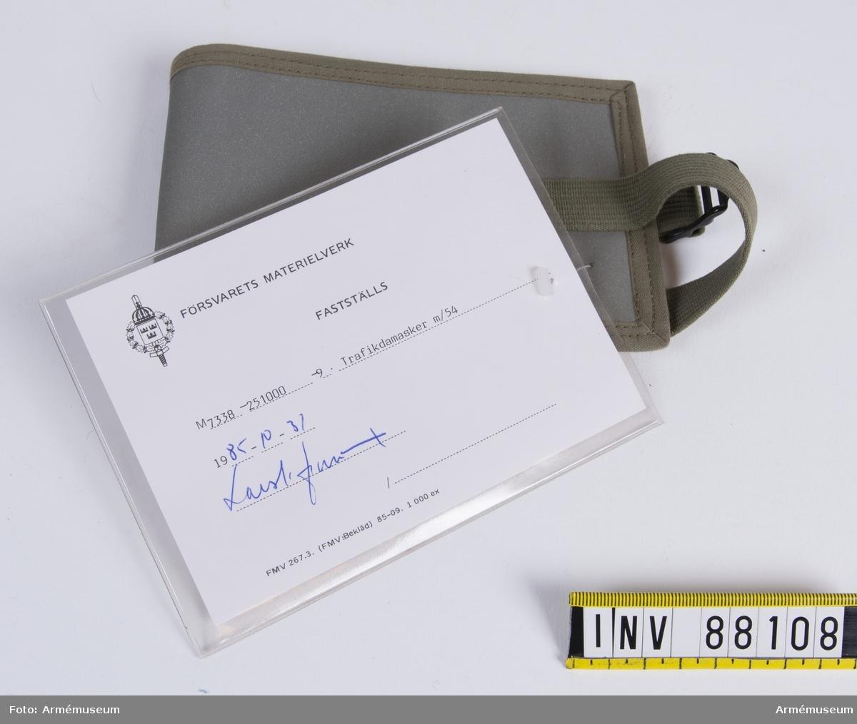 """Damasker bestående av ett rektangulärt stycke brunt tyg med reflexväv på utsidan. De två lagren hålls samman med en grön kantslå. Damasken fästs med ett vävt band och metallspänne. På tygsidan är Palmgrens firmamärke stämplat. Vidhängande modellapp med text: """"Försvarets materielverk. Fastställs. M 7338-251000-9. Trafikdamasker m/54. 1985-10-01-31. (oläslig signatur)"""""""