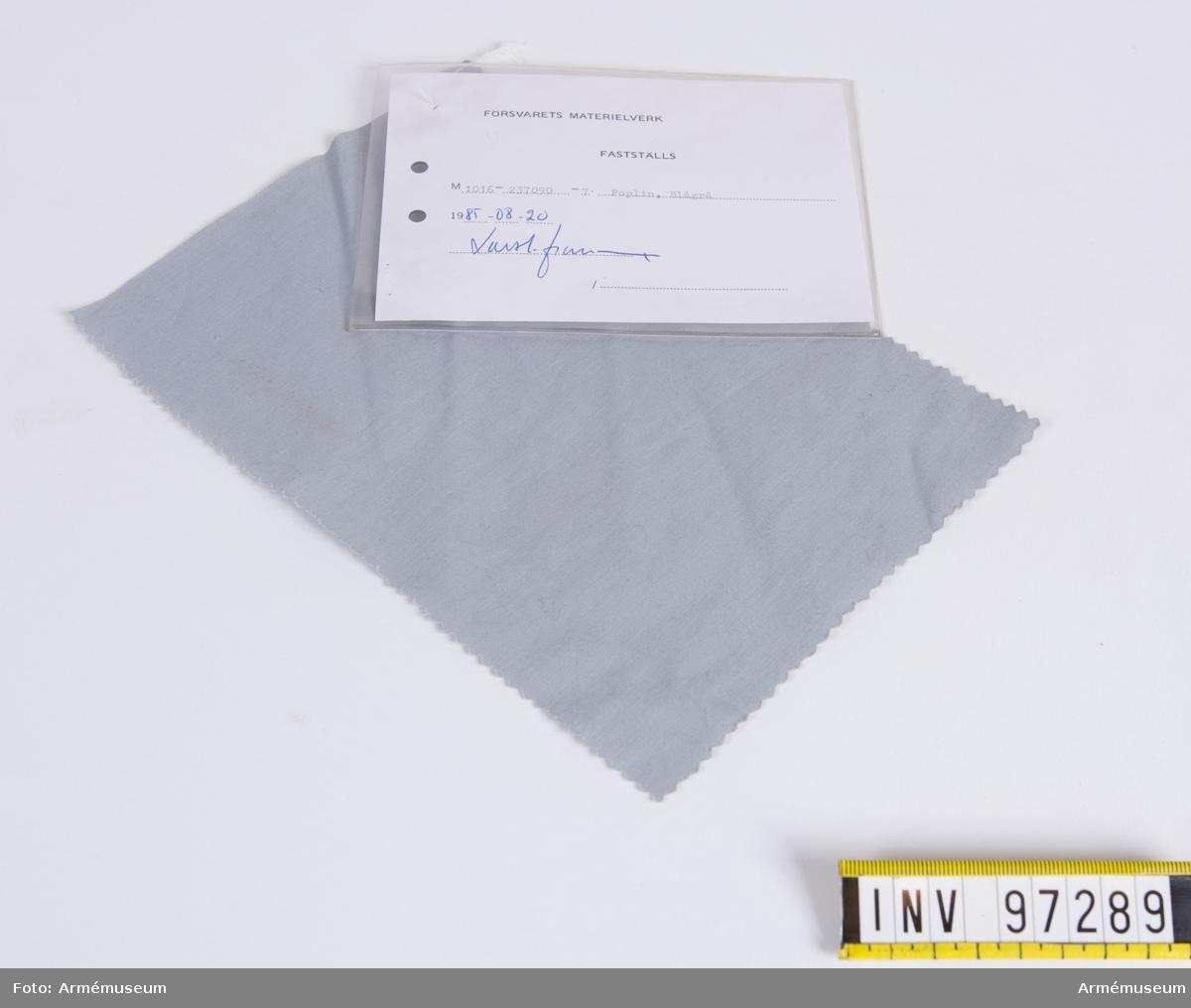 """Vidhängande modellapp med text: """"Försvarets materielverk. Fastställs. M 1016-237090-7 Poplin, Blågrå. 1985-08-20. (oläslig sign)"""""""