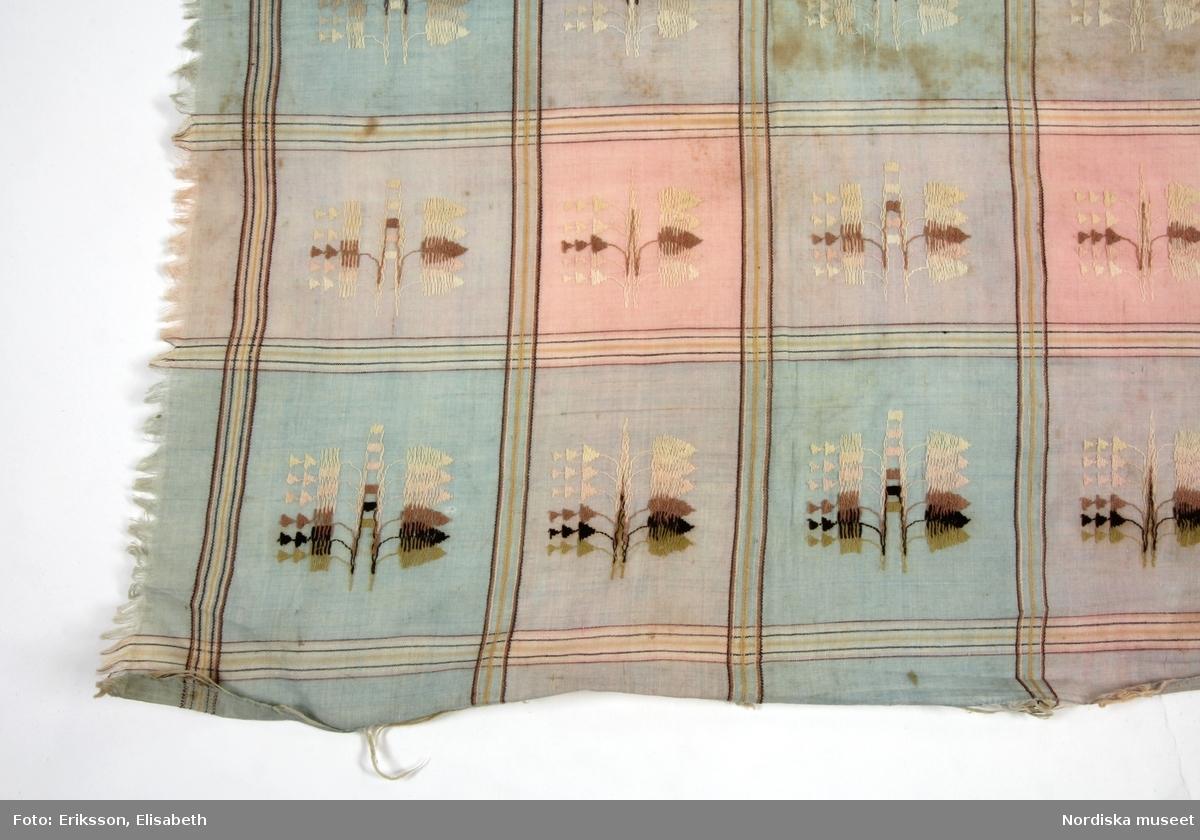 Stort kvadratiskt huvudkläde eller halskläde av tuskaftat bomull,  storrutigt i vitt, rosa och ljusblårr med rutorna avgränsade med tunna gula och bruna  ränder. I varje ruta invävt ett nonfigurtivt motiv med extra varptrådar i något grövre bomullsgarn i  flera vit/brun/rosa färger som schatterar i varandra. Varptrådarna har rört sig i sidled,  huvudsakligen på rätsidan, genom s.k. lappet weaving, och klippts av mellan varje figur så att de förefaller broscherade, en skotsk uppfinning som användes redan under början av 1800-talet. Upprispad frans runtom. Se även klädet  162.565 från Småland Anm. Något fläckig /Berit Eldvik 2012-01-30