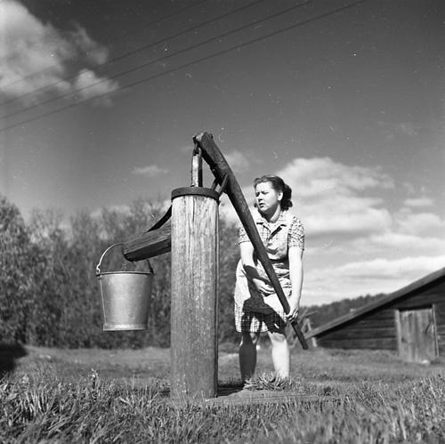 En kvinna står på gårdsplanen vid Sörgården i Västerböle och pumpar vatten från vattenpumpen in i en hink.