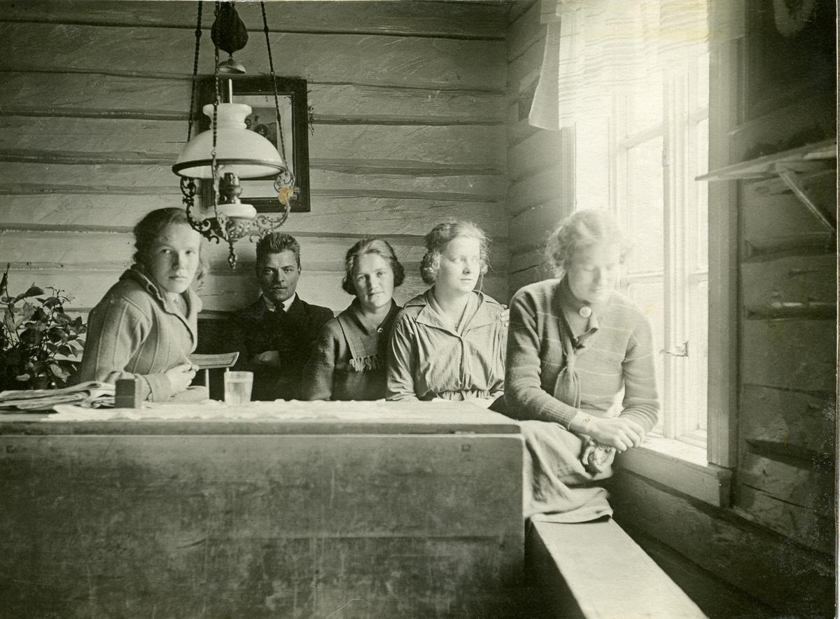 Fire kvinner og en mann i en skolesal. Personene er ukjente.