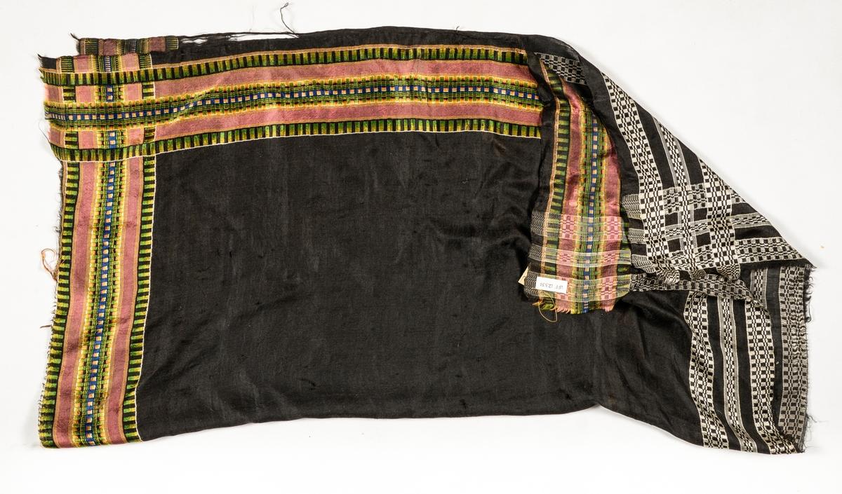 Tørkle i svart silke med kjerringtannbord i grønt, gult, rosa, blått og kvitt i to sider, og bordar i kvitt og svart i dei to andre sidene. To-preikeplagg.