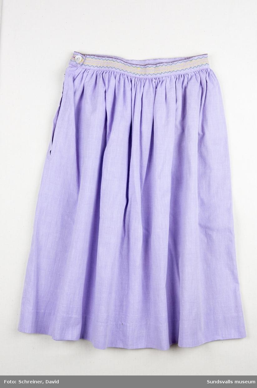 En lila barnkjol med två maskinbroderade och spetskantade fickor. Linningen i midjan bär samma utsmyckning som fickorna. Kjolen har en infälld dragkedja i sidan.