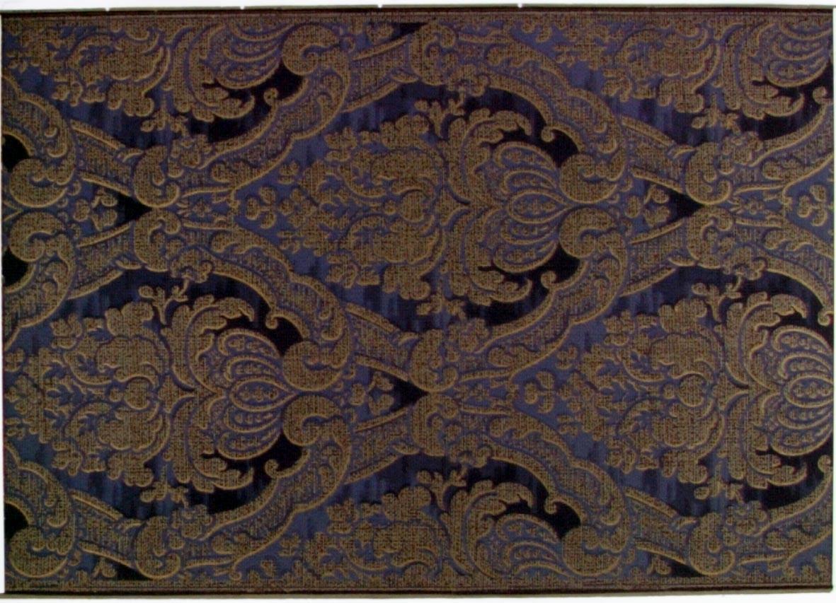 Liljeliknande blommor i diagonalupprepning. Tryck i svart och guld samt i flera blå nyanser. Beigegrått genomfärgat papper.