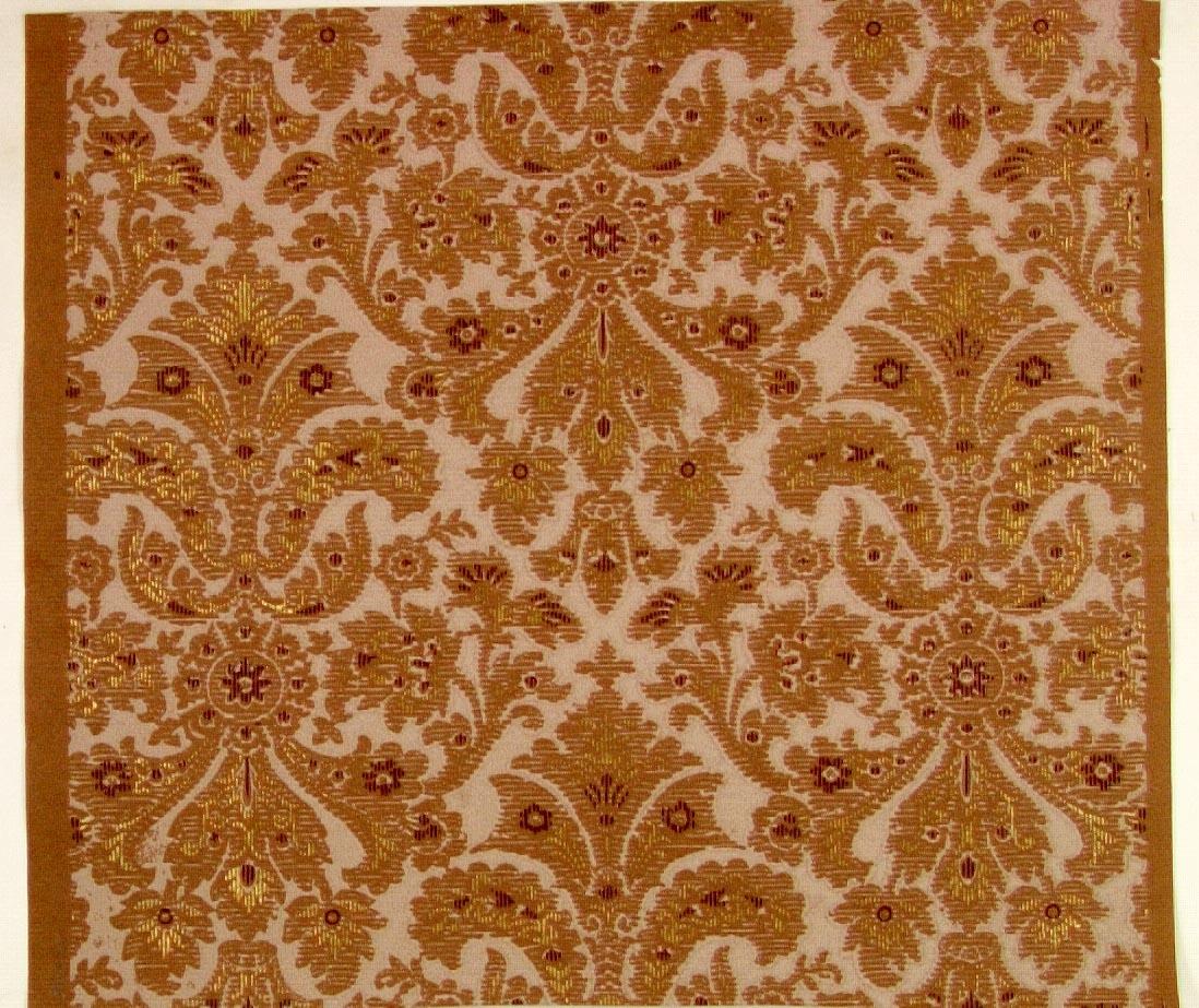 Ett symmetriskt mönster med liljeliknande former i diagonalupprepning. Tryck i vinrött, guld och ljuslila på ett ljusbrunt genomfärgat papper.
