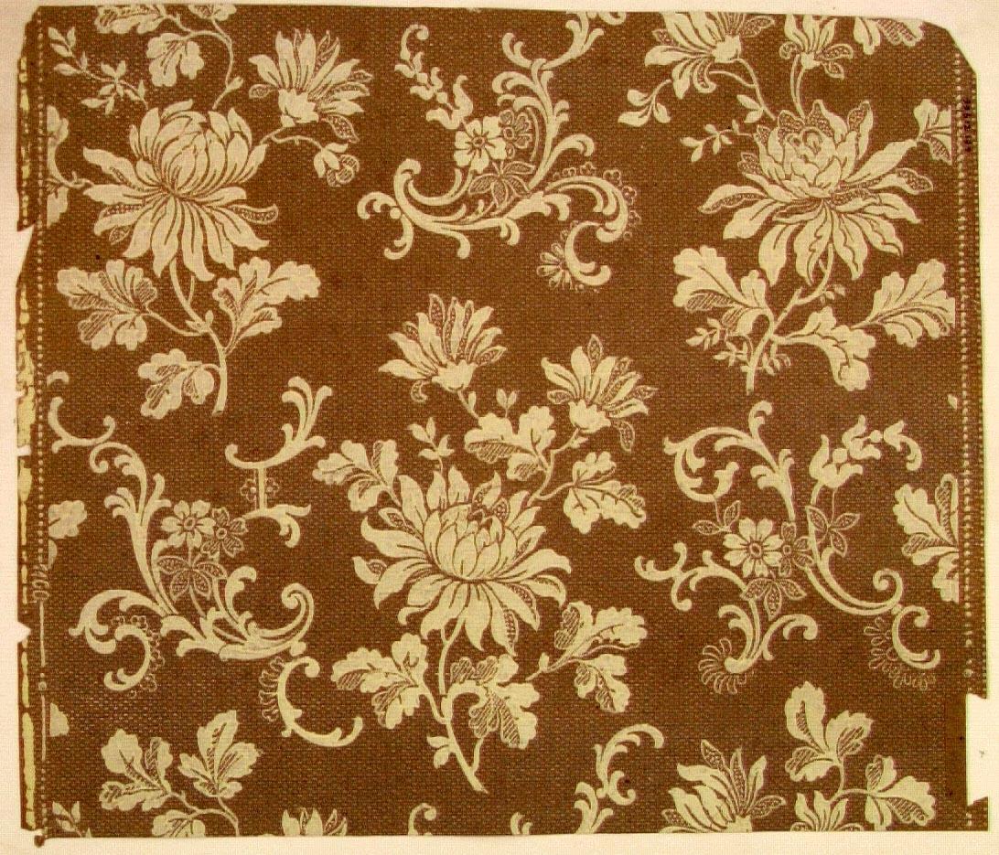 Blommor dekorerade med invecklade rocaille-ornament i diagonalupprepning. Tryck i cremevitt på ett ljusgrått genomfärgat papper. Övertryck med streck-/prickmönster.