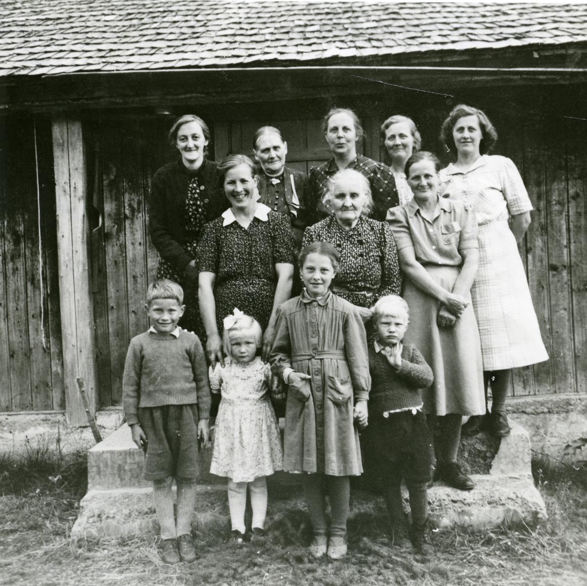 Kvinner og barn på trappa til et stølshus på Svartsetra.
