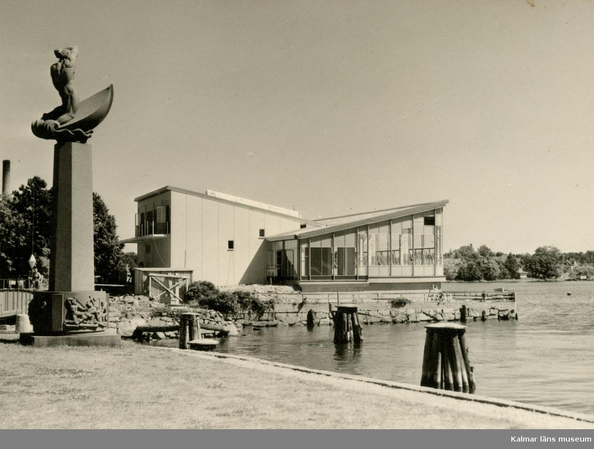 """Restaurang Slottsholmen är byggd i modernismisk stil som  karakteriseras av en avskalad och geometriskt enkel arkitektur då det är själva formerna och konstruktionen som står för det arkitektoniska värdet. Skulpturen """"Spejande sjömannen"""" Den 15 juni 1950 brann den """"gamla"""" restaurangen ned. Den 18 november påbörjades uppförandet av den nya restaurangen, som invigdes den 17 juli 1952. För publicering av bilden hänvisas till ägaren via Kalmar läns museum"""