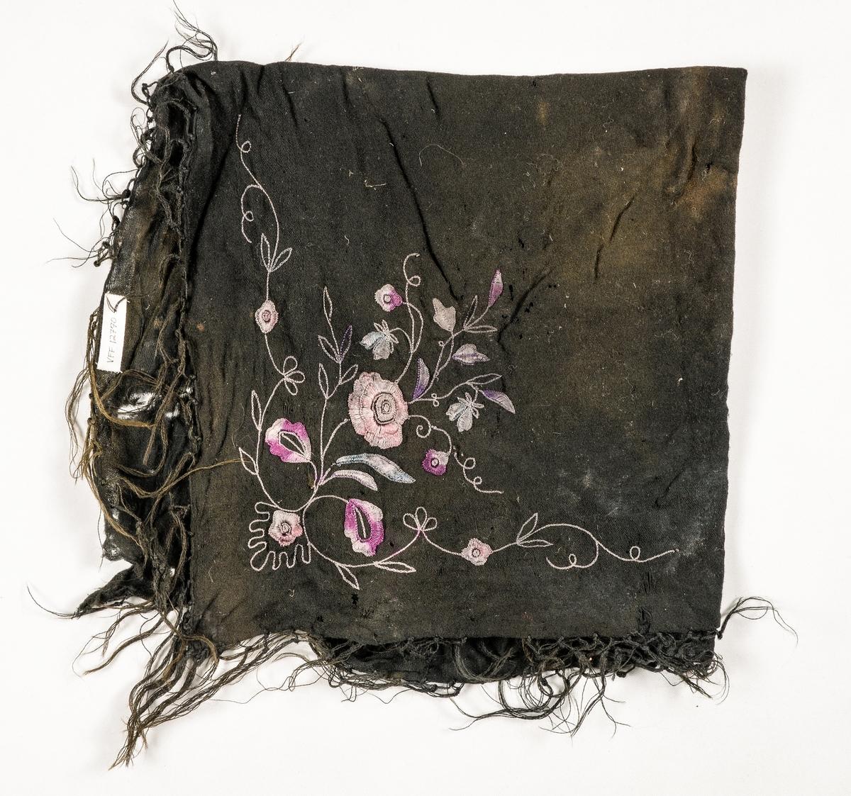 Tørkle i svart ullmusselin. Brodert blomstermotiv i to fiolette fargar, blått og rosa i eine hjørnet. Falda på to sider, jarekant på dei to andre. Påsette knytta ullfrynser.