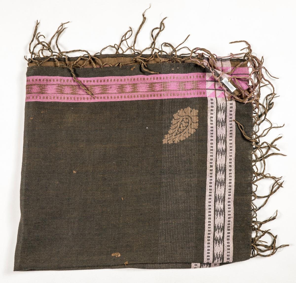 Tørkle i bruntsvart damask med mønsterbordar langs sidene i lilla, rosa og fiolett. Bomull i renning og ull i innslag. Falda (tråkla) på to sider, jarekant i dei to andre. Påsydde og knytta frynser i brunt, rosa.