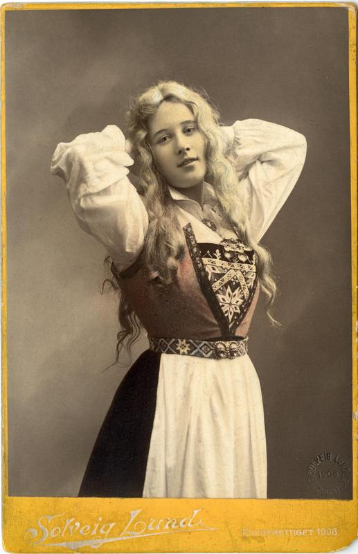 Kolorert studiofotografi av kvinne med harangerdrakt og utslått  hår. 1906. (Foto/Photo)