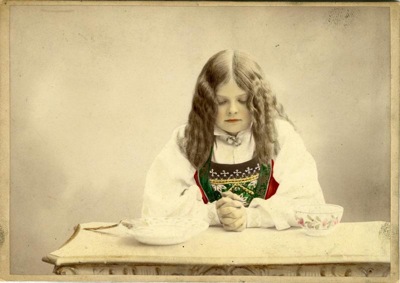 Kolorert studiofotografi av jente med Hardangerdrakt, sitter med foldelde hender på bord. 1903.