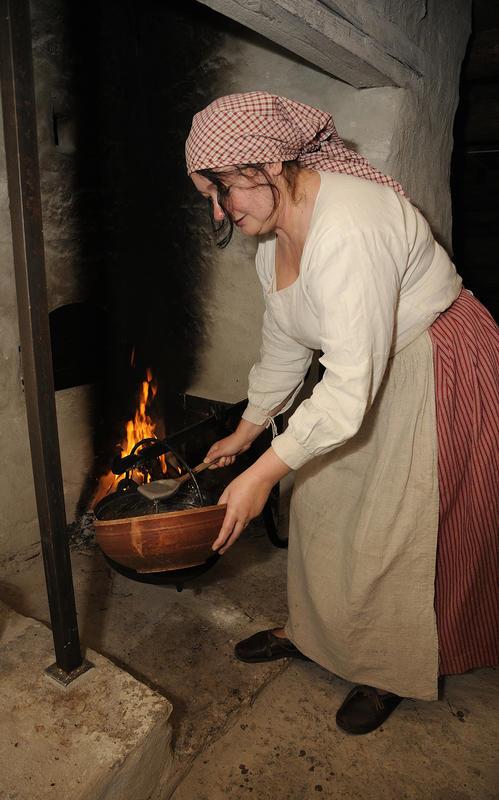 Kvinne med rød stakk, hvit langermet trøye, grått grovforkle og rødrutete skaut står foran den åpne ilden i grua og øser grøt fra ei stor gryte opp i en rundt trefat. (Foto/Photo)