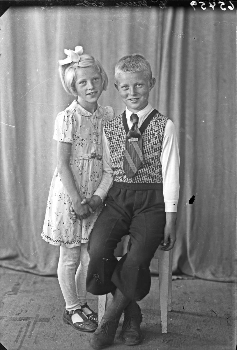 Gruppebilde. Familegruppe på to. Ung gutt og ung pike. Bestillt av Marie Tveita. Auklandshavn.