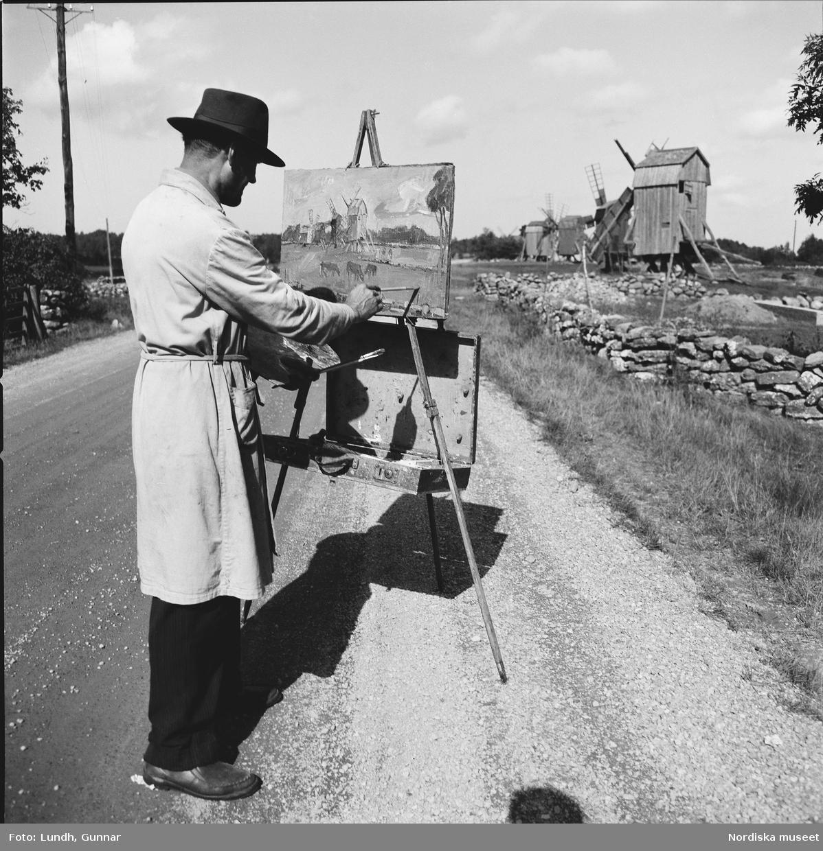 En konstnär i hatt och målarrock står vid ett staffli på en grusväg och målar av kvarnar bakom en låg stenmur.