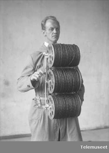 Person som bærer kabelruller med ledning for felttelefon på bæremeis, Elektrisk Bureau.