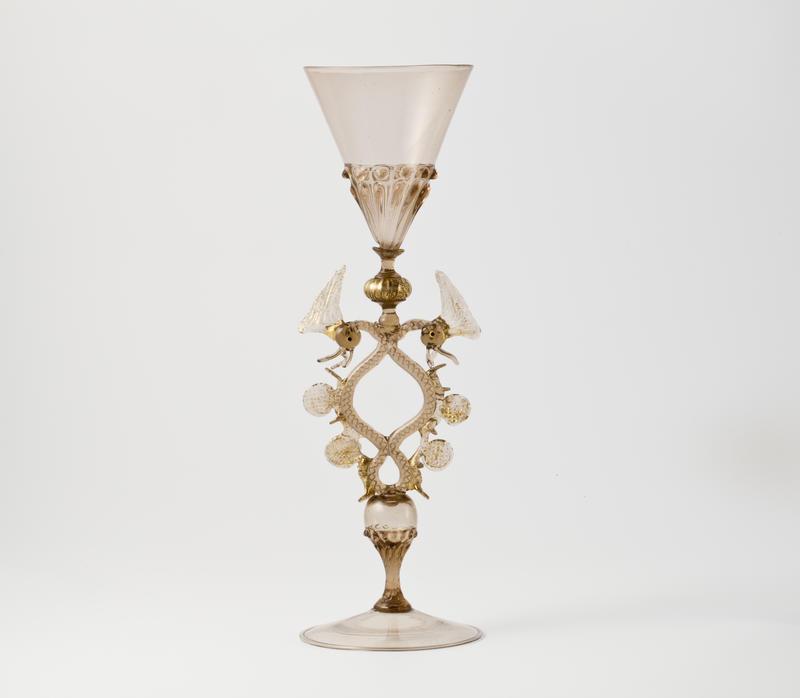 Tynt, gjennomskinnelig bruntonet glass. Spiss kupa med plastiske relieffer rundt nedre del. Glasset ben er dekorativt utformet som en stilisert orm med to hoder som bukter seg mot benet.