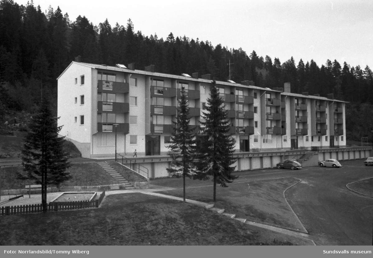 Nya flerfamiljshus vid Ludvigsbergsvägen 12-20. Exteriörbiuld samt från balkongen och köket hos en familj. Två barn på balkongen och en kvinna i köket.