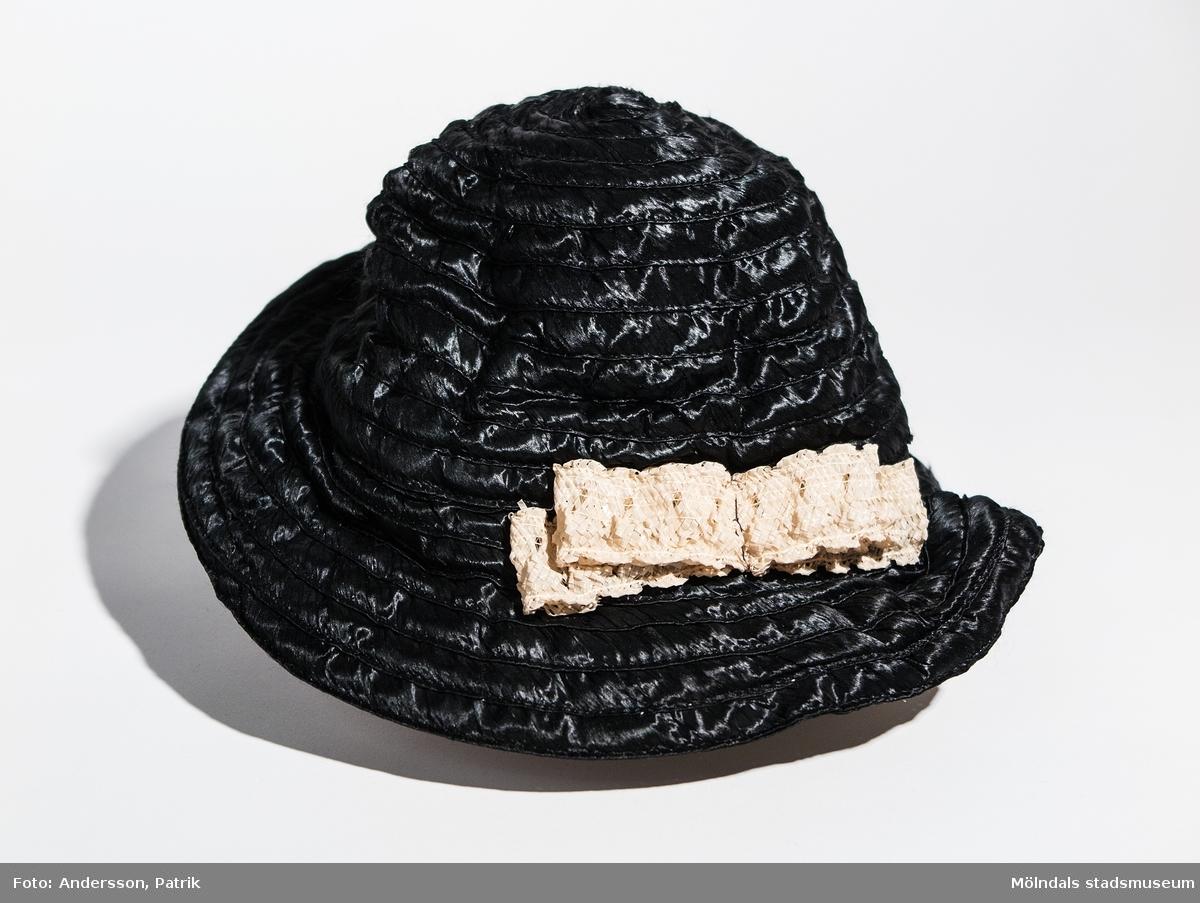 Damhatt inköpt i Eskilstuna, troligtvis på 1930-talet. Hatten är svart. Den har vit spets som detalj fastsydd på vänster sida av hatten och har ett svart gummiband som hakband. I hatten finns en etikett fastsydd med texten:  TEL. 3199 Elsie ESKILSTUNA KÖPMANGAT.52  Enligt uppgift från givaren är hatten inköpt på 1920-talet, men eftersom butiken öppnade 1934 är hatten troligen inköpt på 30-talet.