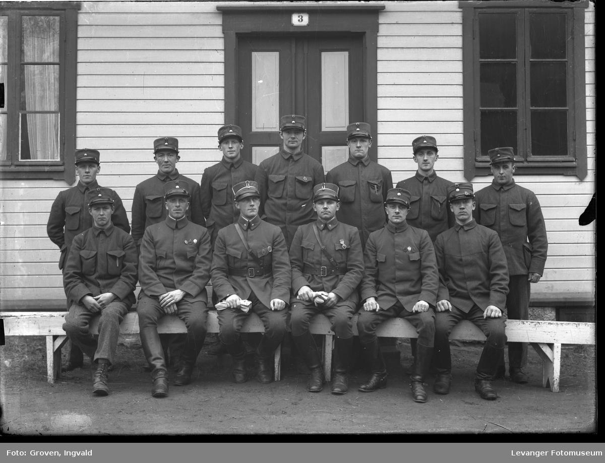 Soldater  foran et hus merket 3, militærbrakke.
