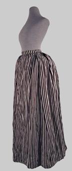 Randig kjol sydd av tuskaftsvävt bomullstyg av tunn kvalité. Tyget är dekorerat med tryckta bruna ränder mot en oblekt botten. Modellen är sydd av fem våder vilka är sammanfogade med små täta förstygn. Kjolen är rynkad runt större delen av midjan. Ett parti mitt fram är slätt. Knäppning med hakar och hyskor i vänster sida, baktill. Nedtill är kjolen skodd med ofärgat glest tuskaftsvävt bomullstyg. Ett smalt flätat bomullsband avslutar kjolen nedtill.