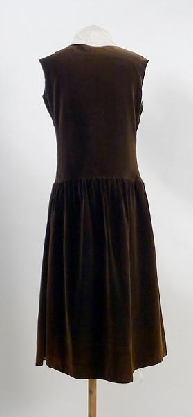 Klänning, barn, sammet. Slätt liv med rund halsringning, kantad med gourgette. Lång blusad ärm av brun gourgette. Rynkad kjol. Ärmar och halsgarnering bortsprättade och söndriga. 20-tals klänning.