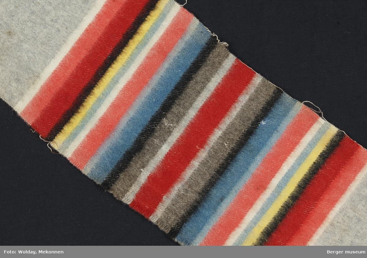En prøve. Striper i grupper hvor stripene gjentas speilvendt. Svært fargerikt. Det ser ut til at det er hele ni farger i dette pleddet. Den skaftestolen som har vevet dette må ha vært mer komplisert enn de vanlige.