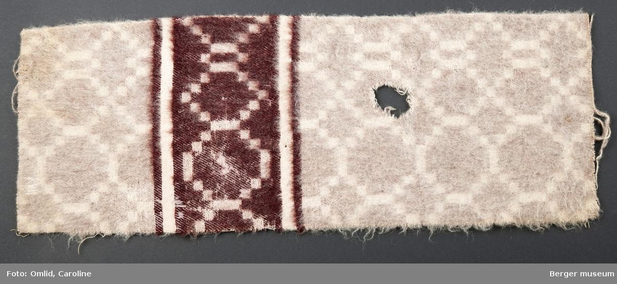 Teppeprøve med åttekantet rutemønster, med bord i liknende mønster innrammet av to paralelle striper. Teppet i lyse beige toner, borden i mørk burgunder