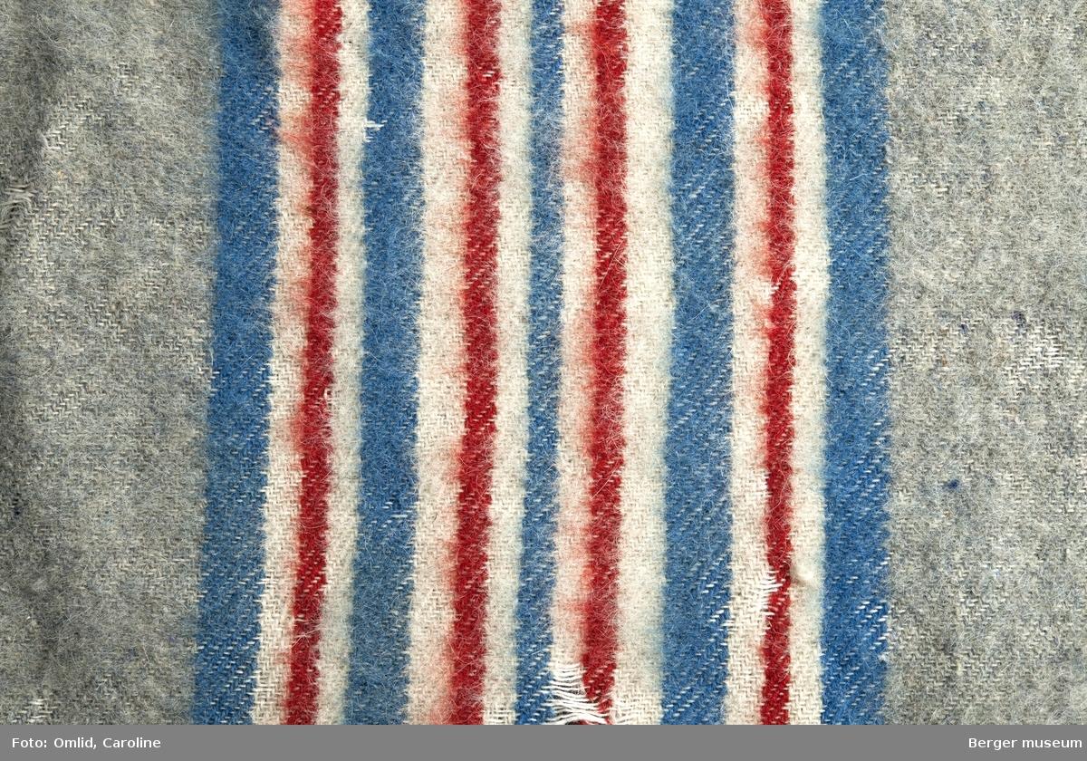 Ensfarget teppe med stripebord med fargene blått-hvitt-rødt-hvitt-blått gjentagende, med fire røde striper. Behandling: Oppfukting med vann i sprayform. Vask i varmt vann tilsatt 1 tsk Berol 784. Innsåping med Marseille-såpe. Skylling i 3 hold varmt vann. Tørking på bord, med vifte, ca. 5 timer.