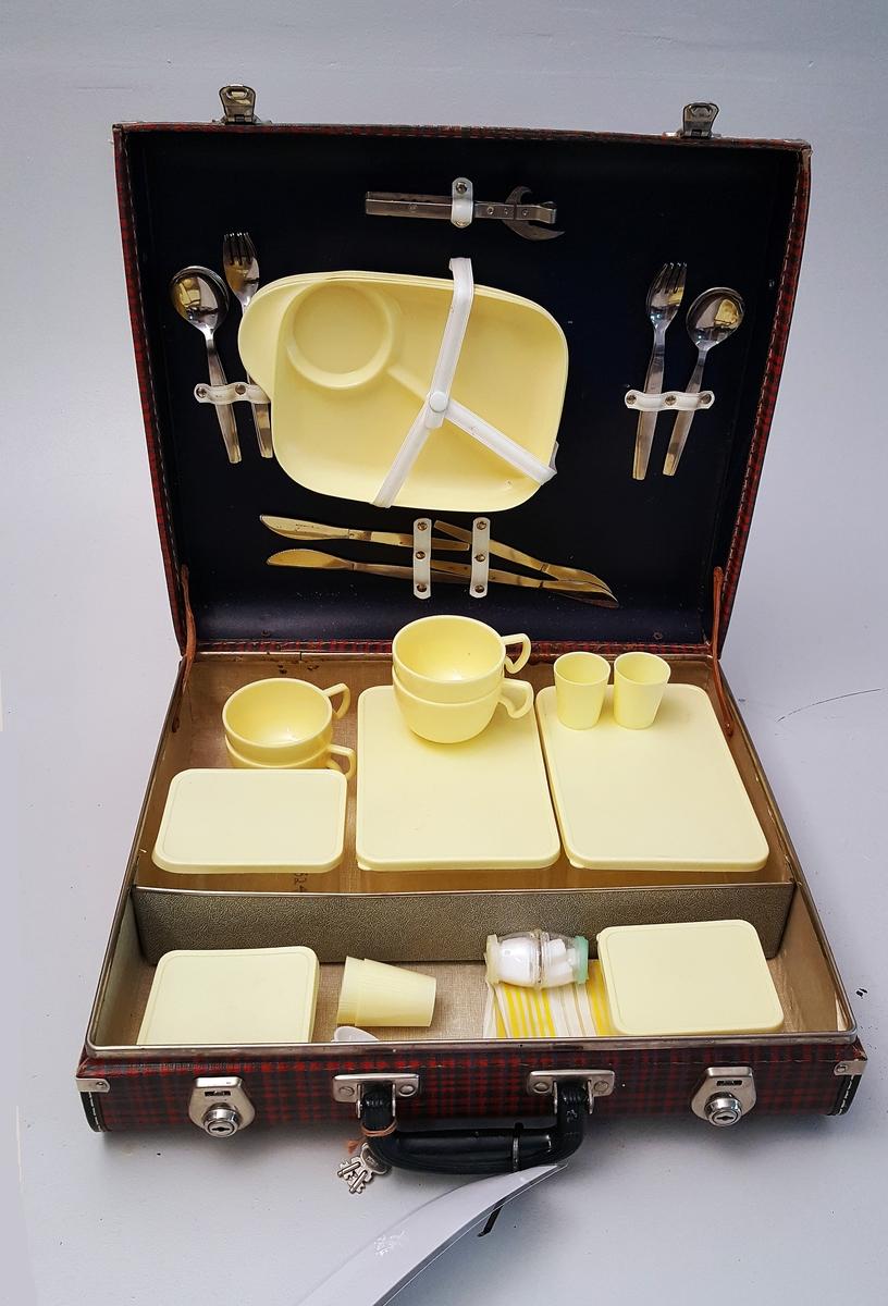 Koffert med servise, bestikk, eggeglas og nisteboksar. 4 koppar, 4 fat, 4 eggeglas, 4 matboksar,            4 skeier, knivar, gaflar, 1 bokseopnar, 1 salt/pepar bøsse.