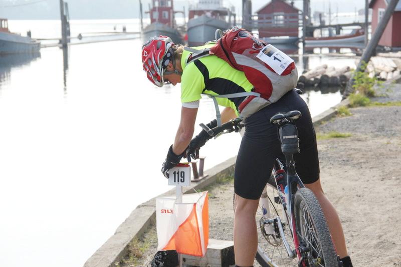 Foto av syklist ved orienteringspost på bryggekanten.