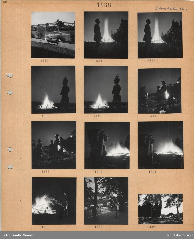 Motiv: Stockholm, park med gräsmattor, gång, träd, plaskdamm, bänk, i bakgrunden flerbostadshus, barn klädda som indianer samt med scoutkläder i kvällsljus vid öppen eld, uteservering på Strömparterren i kvällsljus, Carl Milles staty Orfeus.